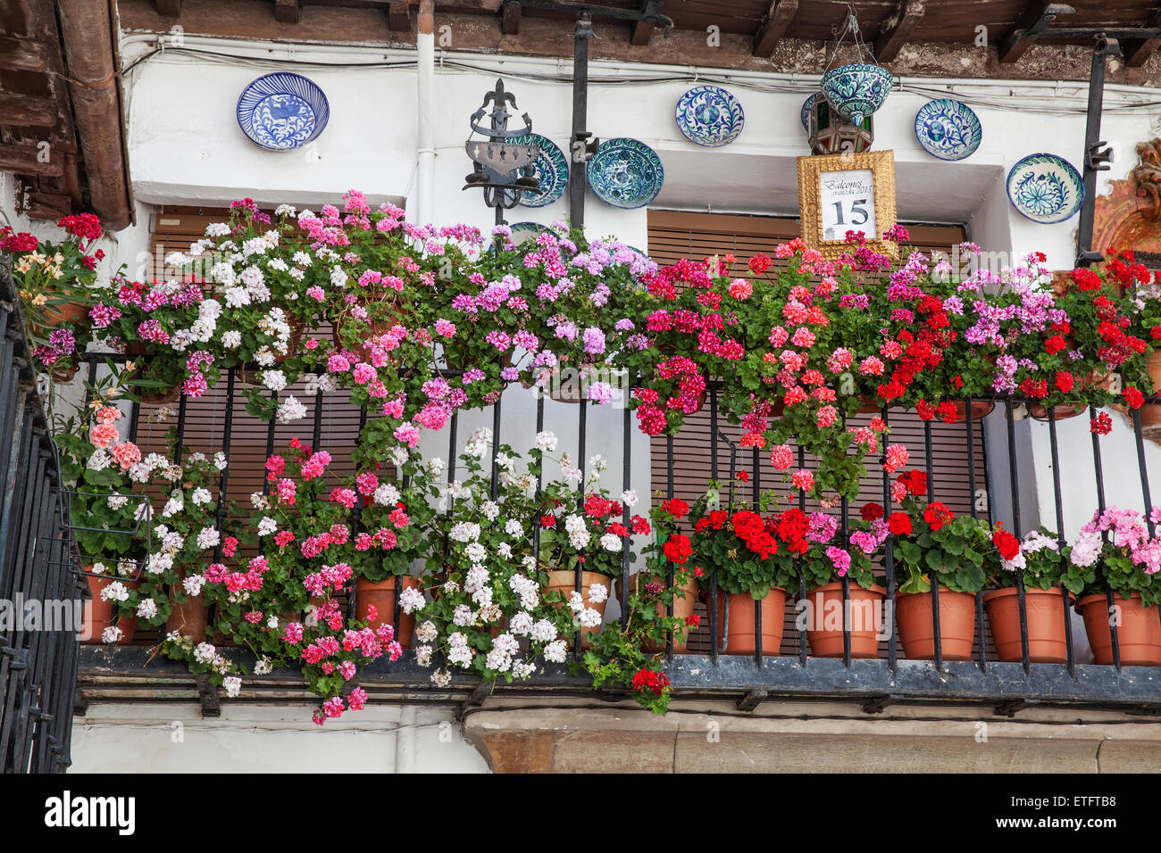 Geranium flower pots displayed on prize winning balcony - Granada, Andalucia, Spain - Stock Image