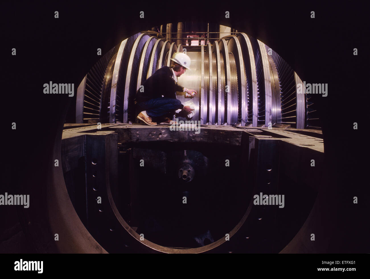 Male engineer inspecting the turbine rotors at a nuclear power plant - Stock Image