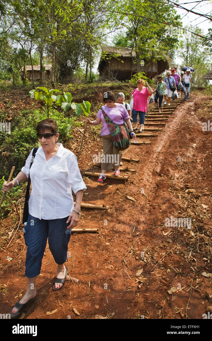 Tourists navigate steps in the hill tribes settlement near Chaing Rai. - Stock Image