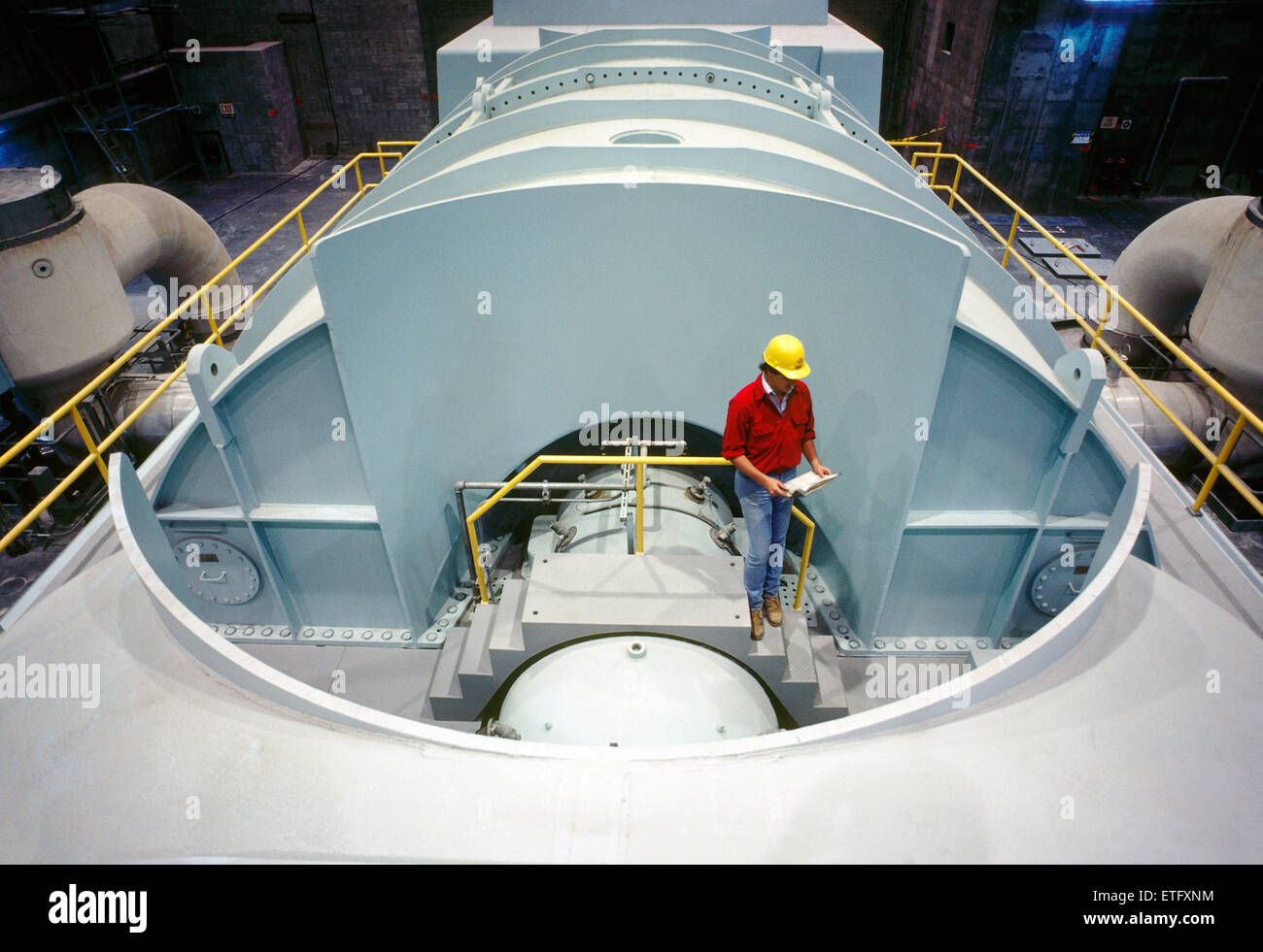 Male engineer inspecting drawings near a steam turbine, nuclear power plant in Pennsylvania, USA - Stock Image