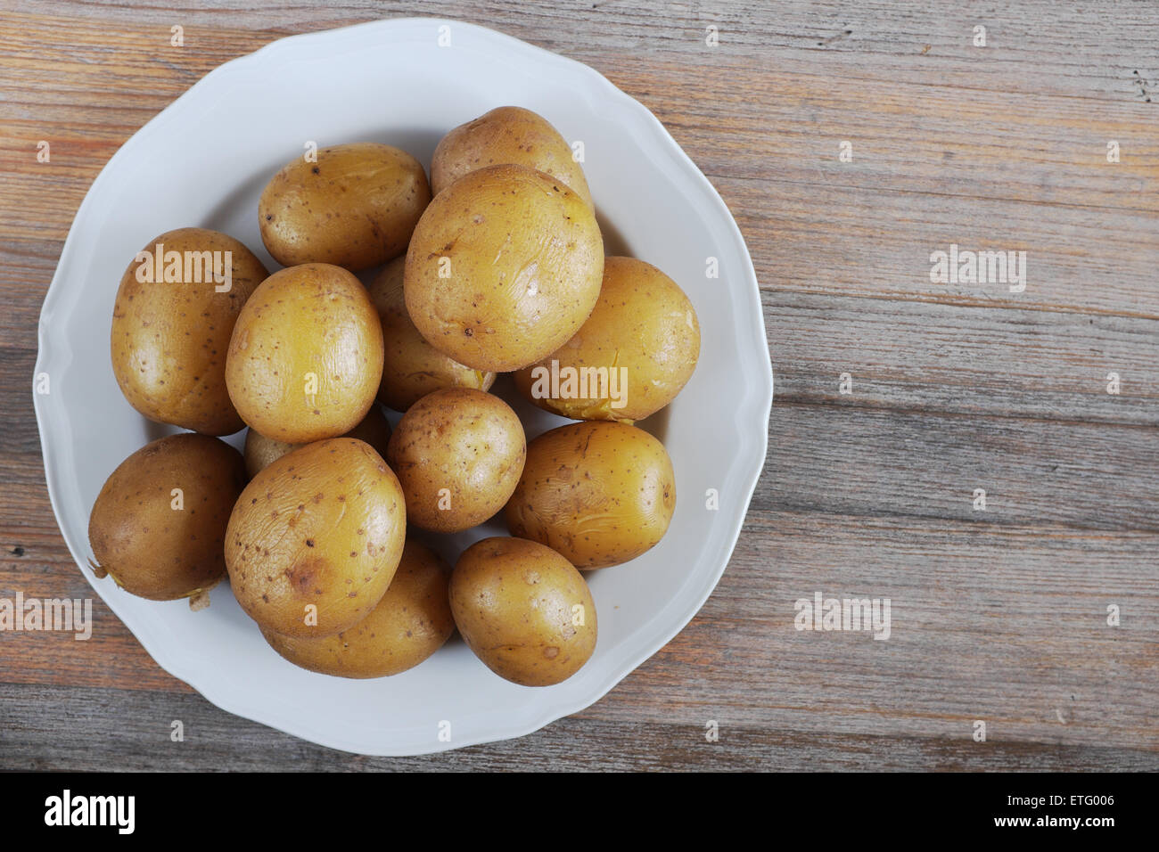 boiled potatoes in their skins on a plate - Stock Image