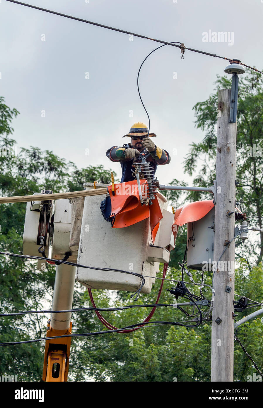 A telcom lineman fixes overhead power lines using a cherry picker, elevated work platform. - Stock Image