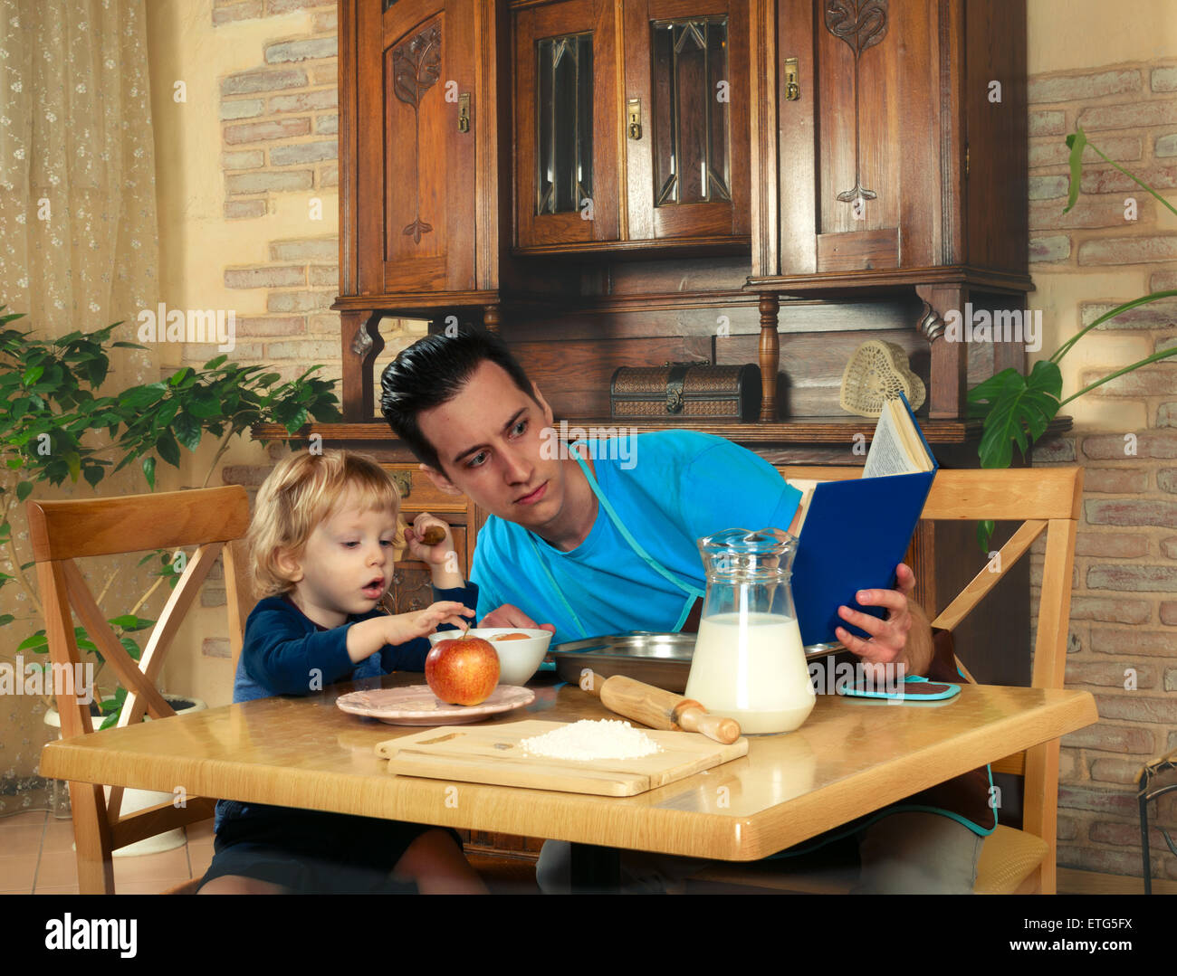 man with little boy in the kitchen preparing a meal. retro - Stock Image