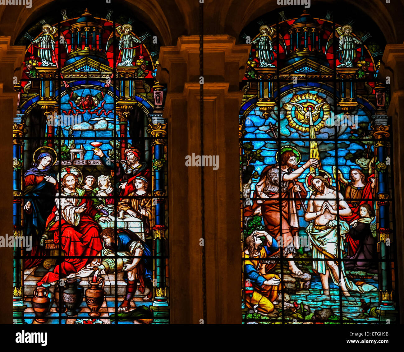 Stained glass window depicting, on the left, Jesus at the Wedding at Cana, and, on the right, Jesus baptized in Stock Photo
