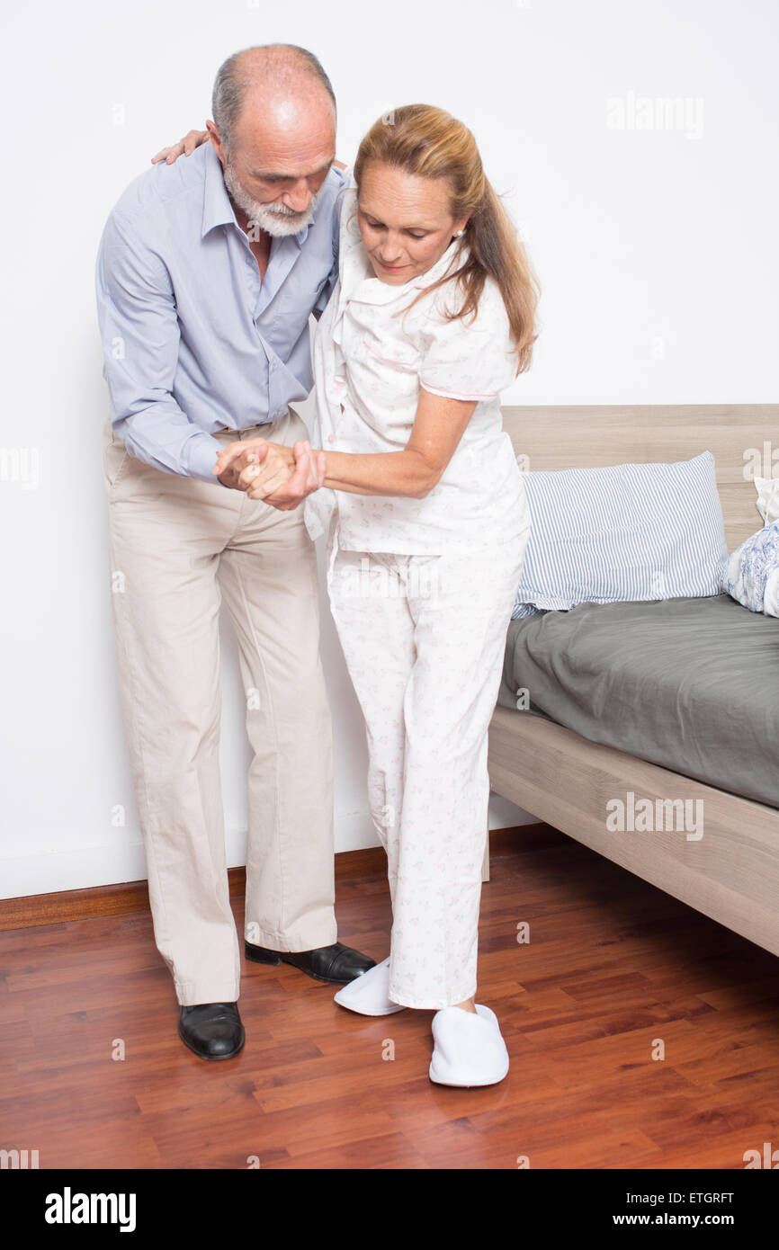 Male nurse helps elderly woman out of bed - Stock Image