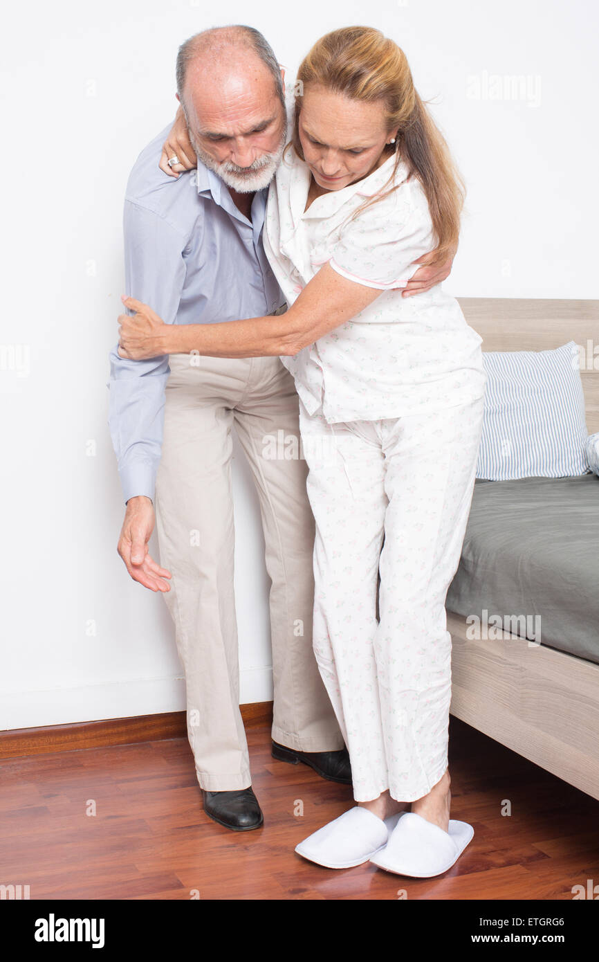 Husband helps wife to get out of bed - Stock Image