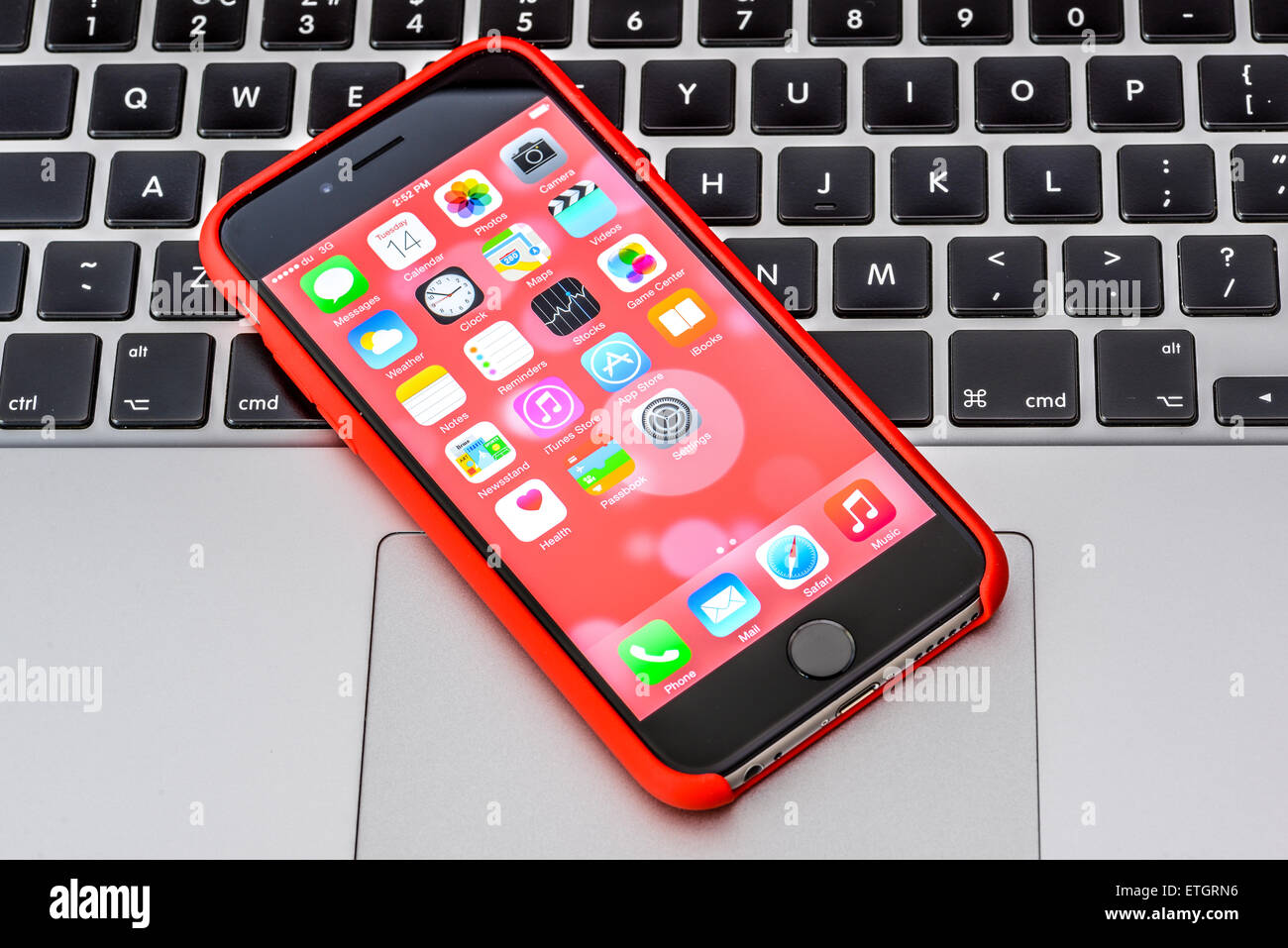 iPhone 6 in red case on an Apple Macbook keyboard - Stock Image