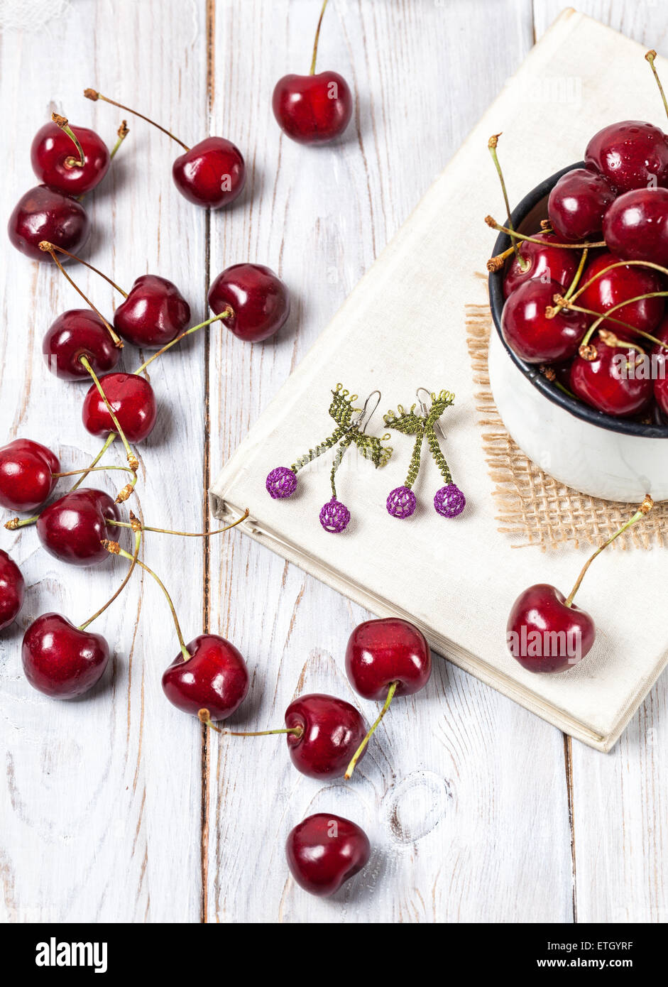 Cherry and handmade earrings on the book and wooden table - Stock Image