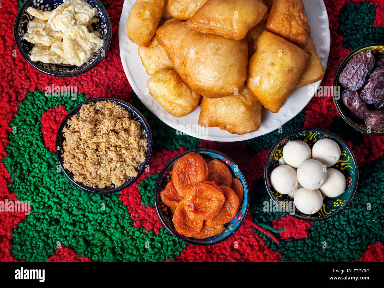 Kazakh national dishes on the carpet with ornament in restaurant - Stock Image