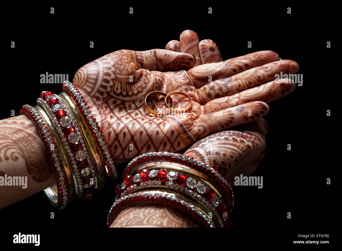 Woman hands with henna holding two golden wedding rings on black background - Stock Image