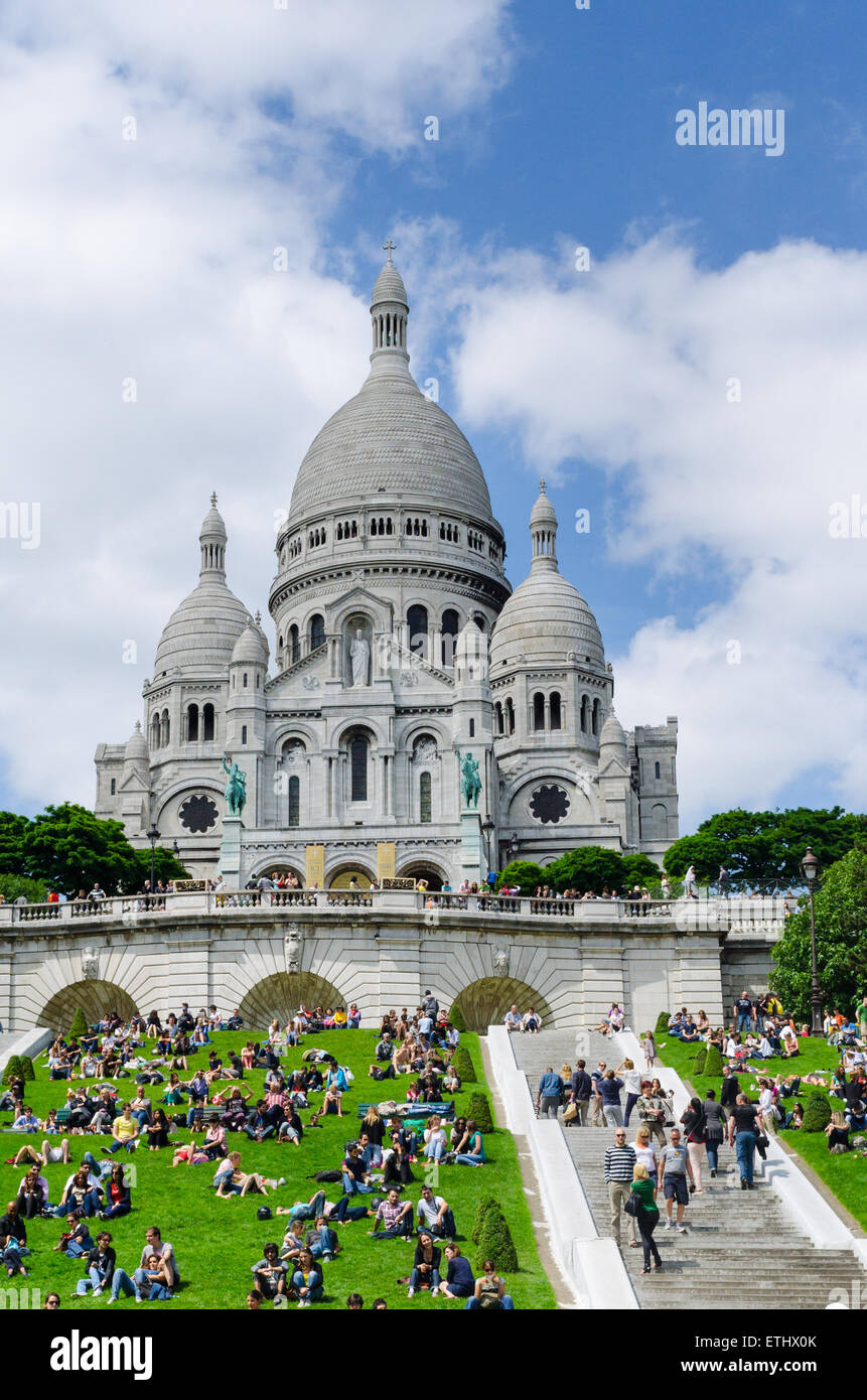 People lying on lawn in front of Sacre Coeur church in Paris, France, vertical - Stock Image
