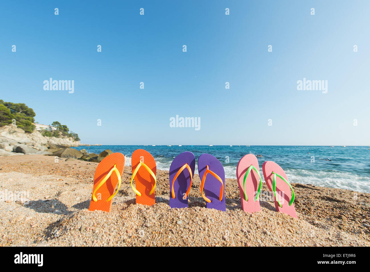 row colorful flip flops at the beach - Stock Image