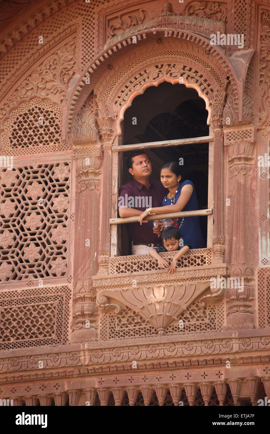Indian family looking out from window in carved facade at Mehrangarh Fort, Jodhpur, Rajasthan, India - Stock Image