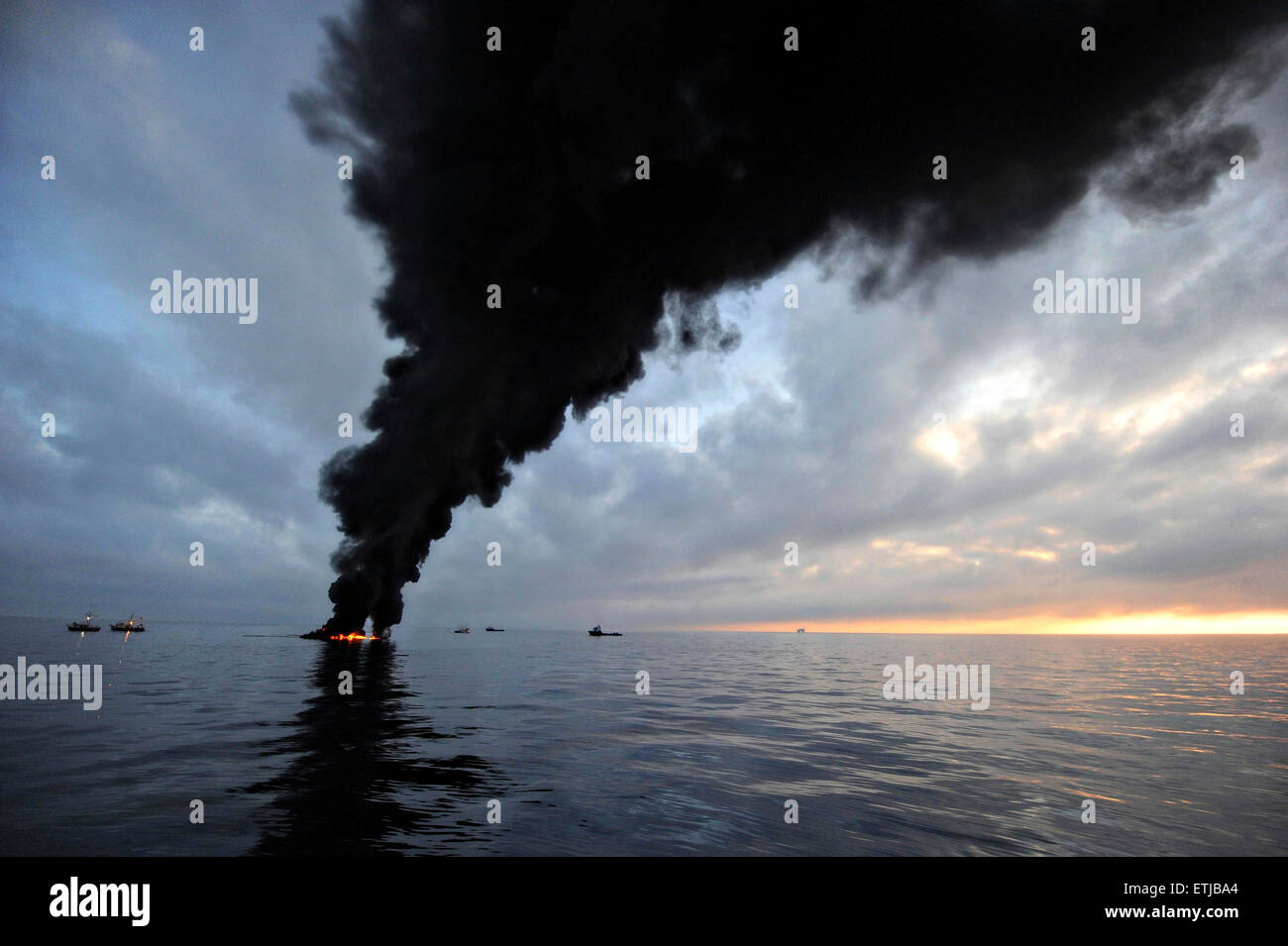 Dark clouds fill the sky as clean up crews conduct controlled burns of oil gathered from the surface of the Gulf - Stock Image