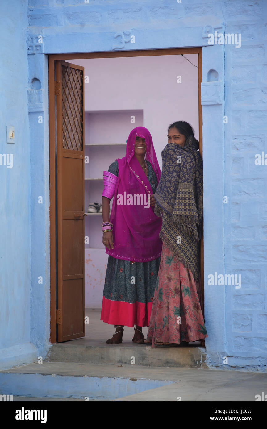 Indian women in colourful saris at the door to their home, Jodhpur, Rajasthan, India - Stock Image