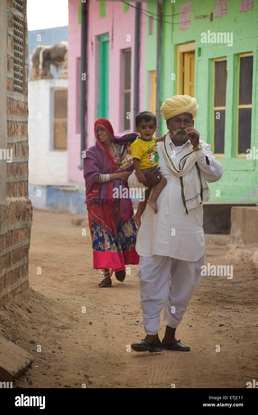 Indian man and woman with children walking down a village street outside Jodhpur, Rajasthan, India - Stock Image