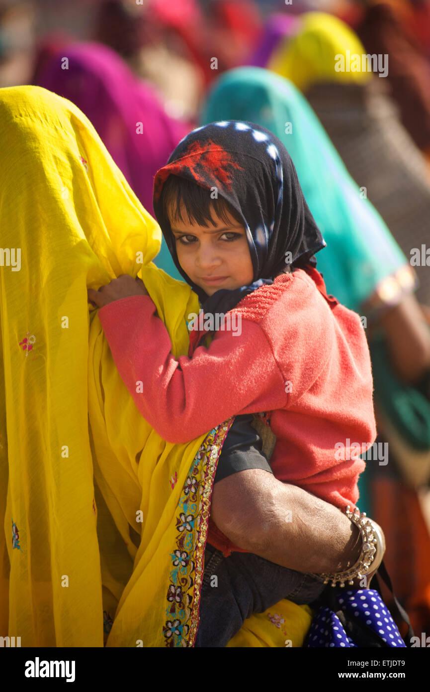Rajasthani woman carrying child, Pushkar, Rajasthan, India - Stock Image
