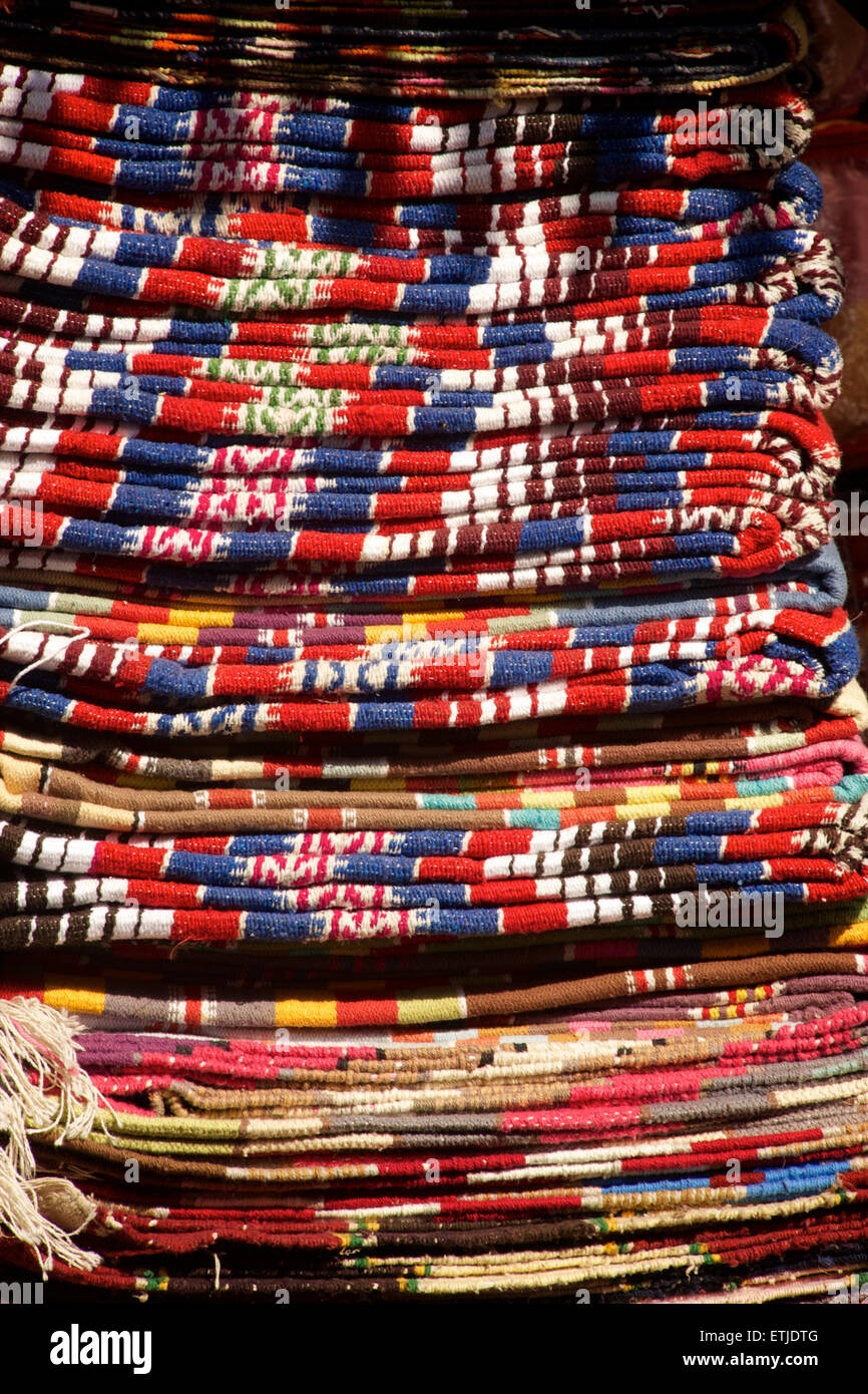 Stack of tapestry rugs for sale in Pushkar, Rajasthan, India - Stock Image
