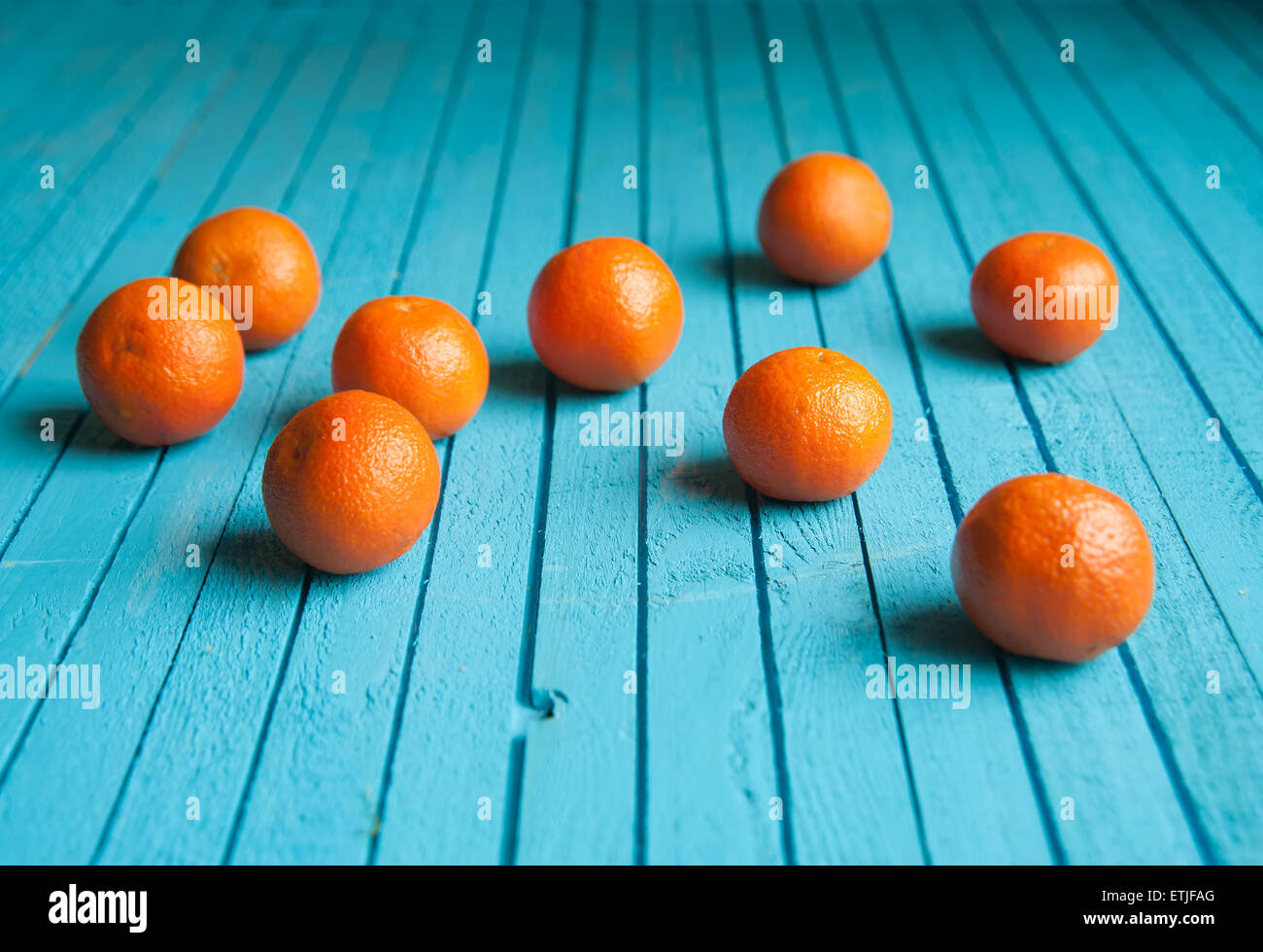 many tangerine lie on a wooden, blue table - Stock Image
