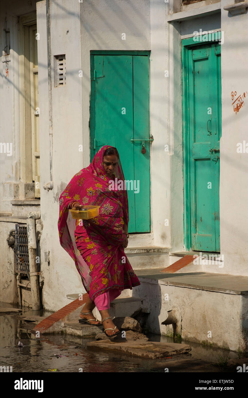 Indian woman in colourful sari walking in the street, Udaipur, Rajasthan, India - Stock Image