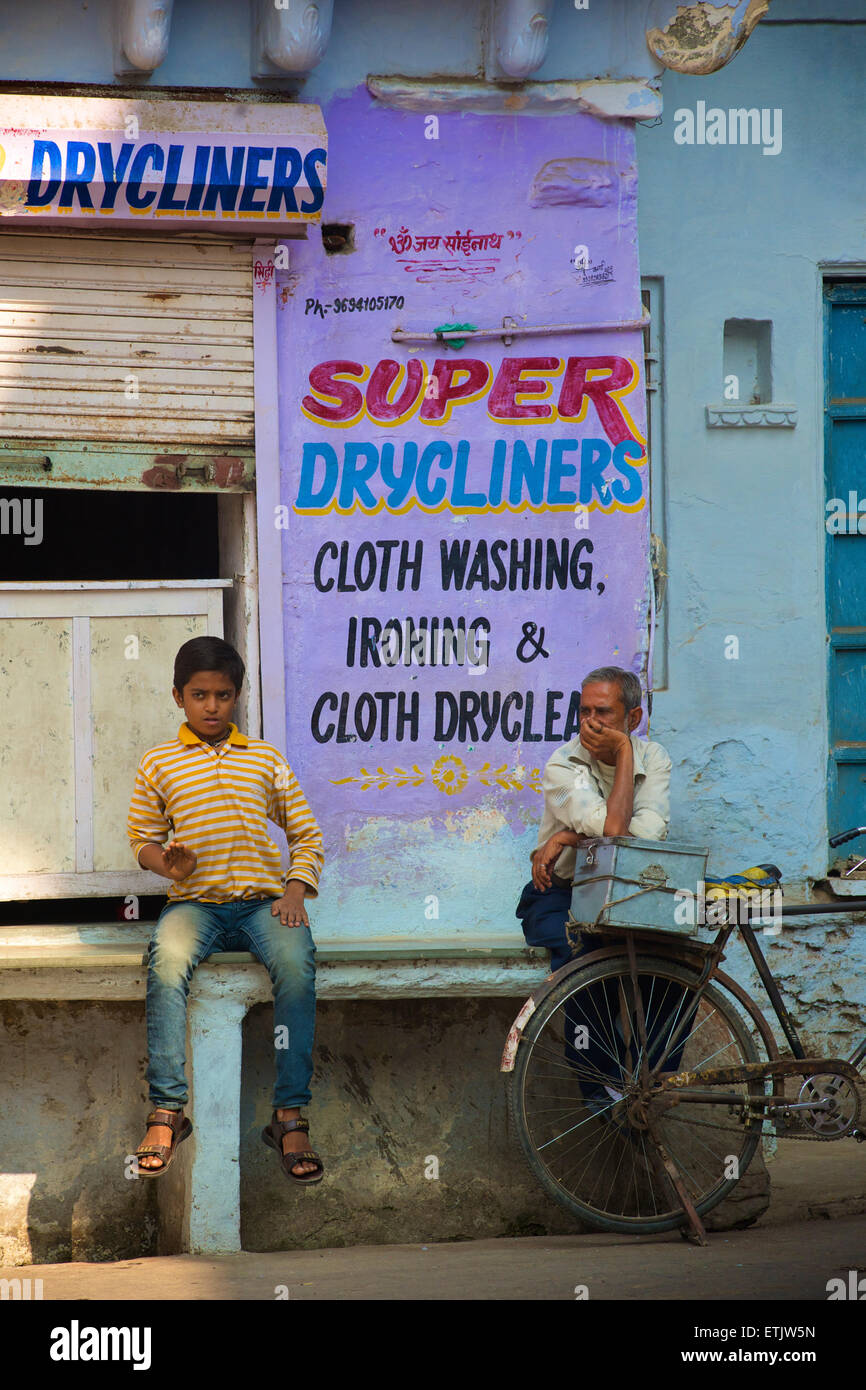 Indian man with bicycle and boy sitting outside a dry cleaners, Udaipur, Rajasthan, India - Stock Image