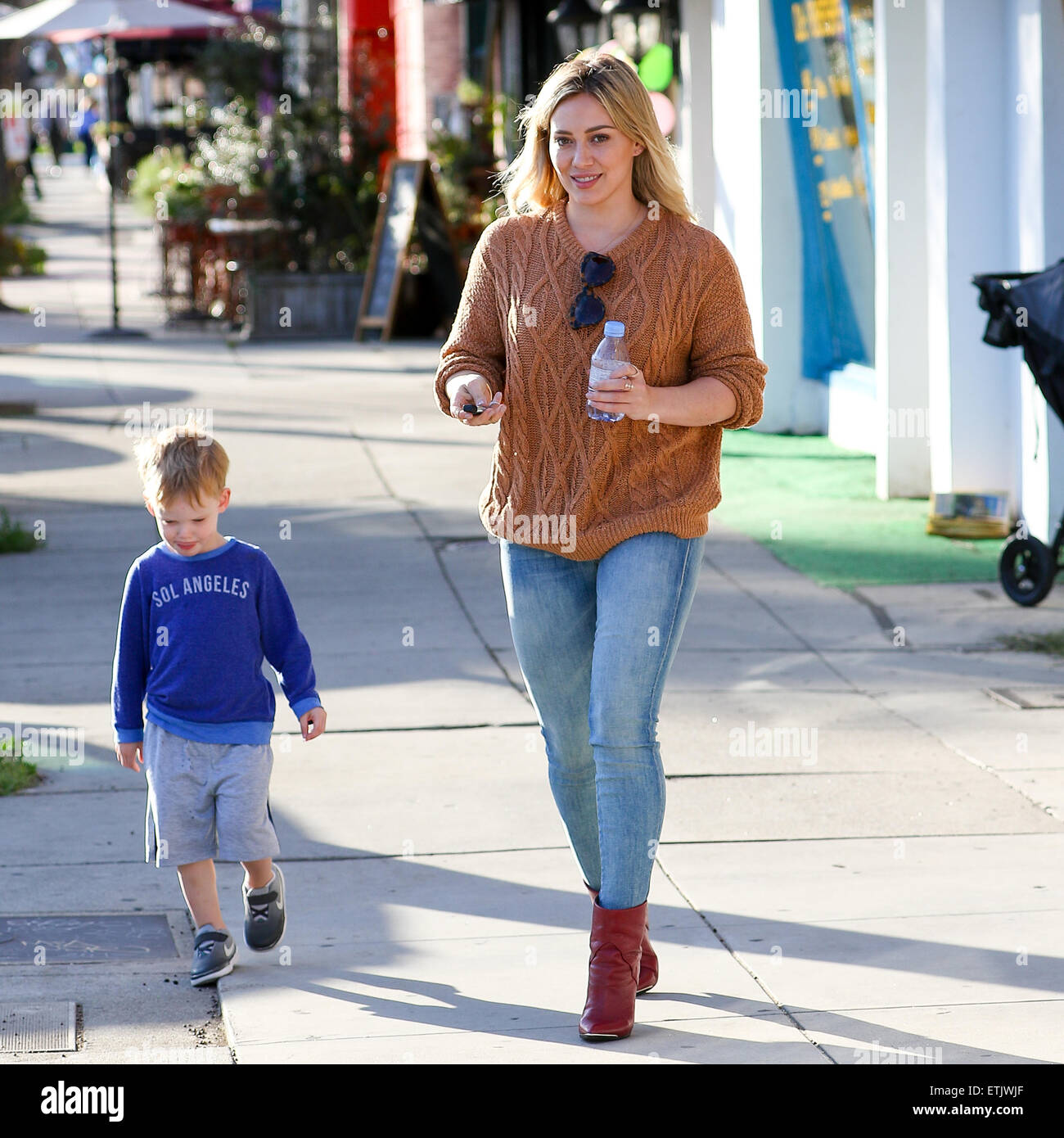 c5f5375a7518 Hilary Duff wearing a bronze woolly jumper with skinny jeans and red ankle  boots