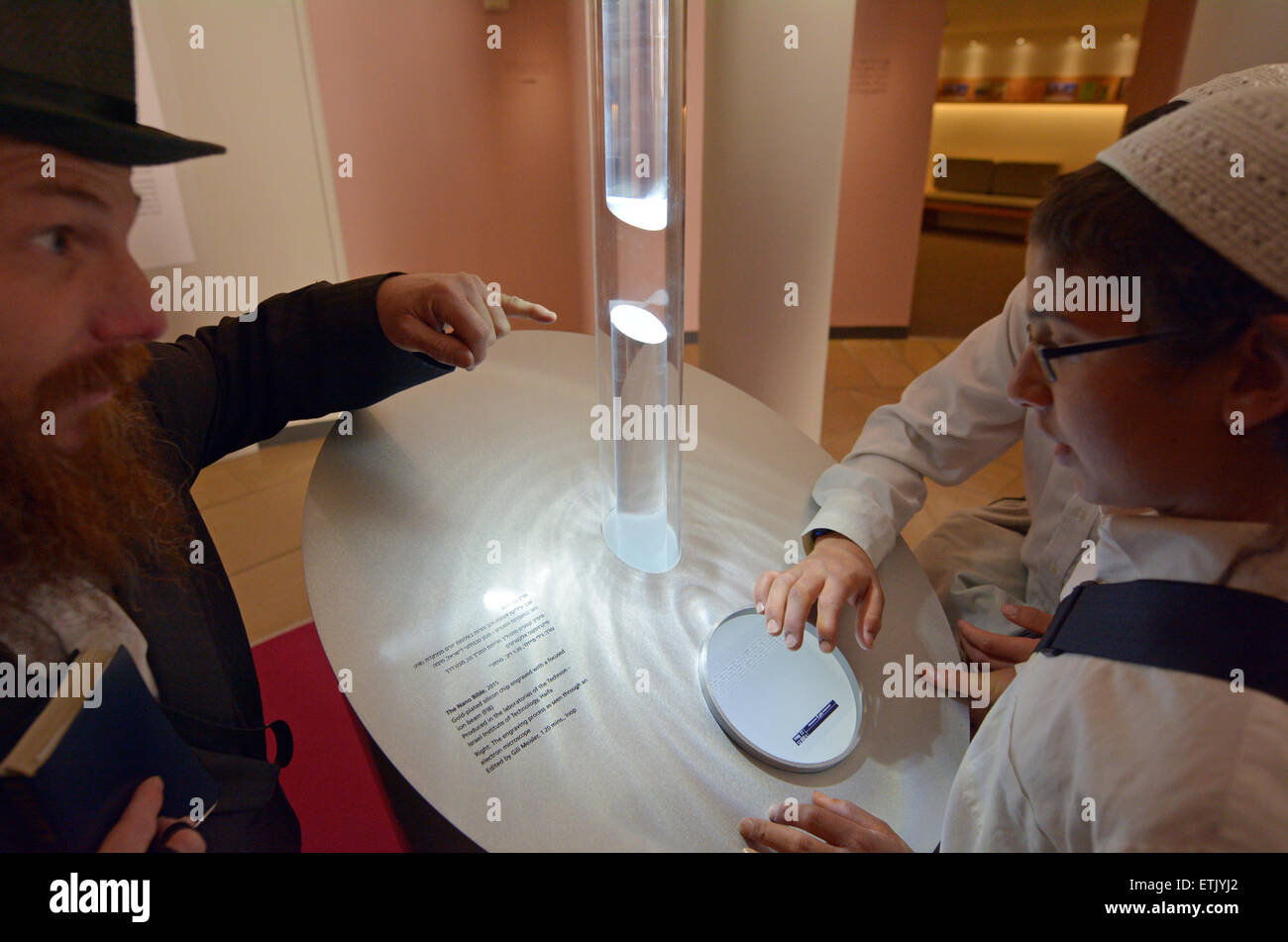 JERUSALEM - MAY 07 2015:Jewish people observe the Nano Bible in Israel Museum in Jerusalem, Israel.The microchip Stock Photo