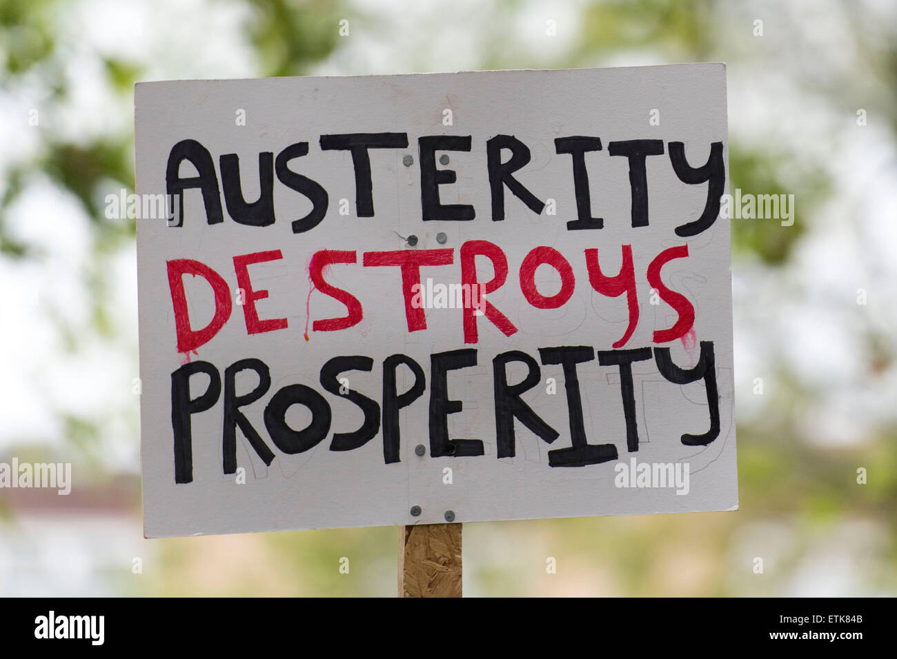 An anti-austerity sign that reads 'austerity destroys prosperity' seen at a protest against the Conservative - Stock Image