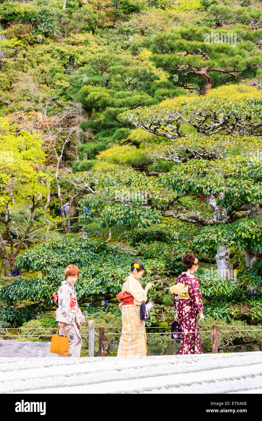 Japan, Kyoto. Three women in kimono walking on path between foods behind them and raked sand in front of them. - Stock Image