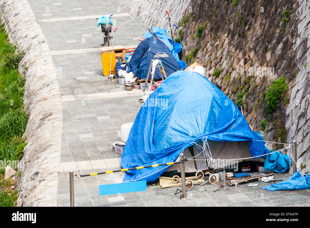 Japan, Kyoto. Blue tarpaulin homeless shelter on river bank, various belongings arranged along walkway by river - Stock Image