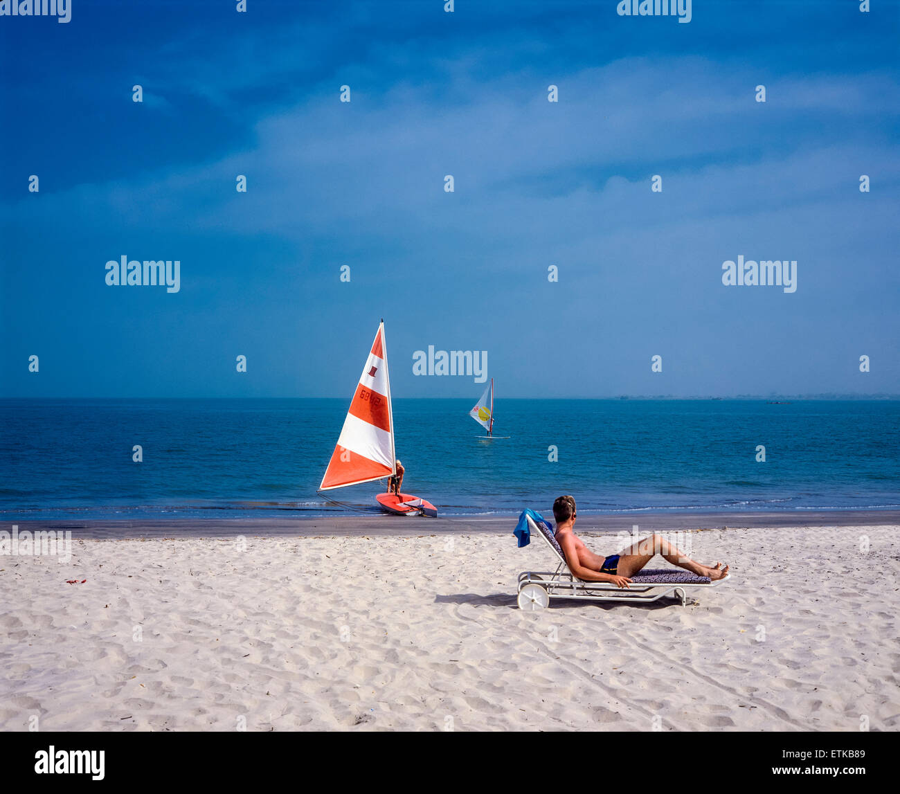 Holidaymaker sunbathing on beach, Gambia, West Africa - Stock Image