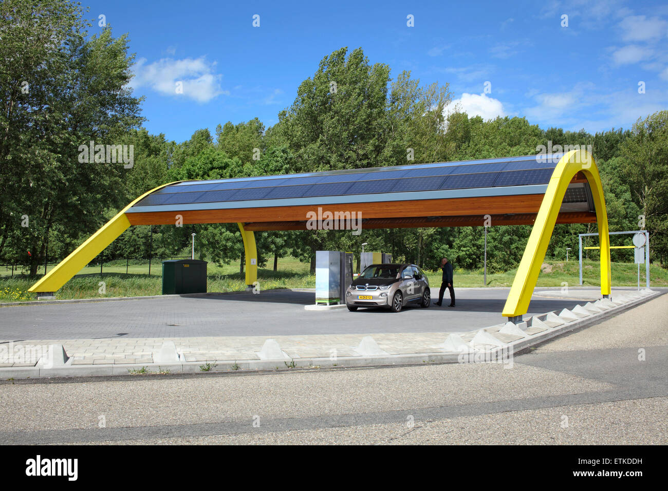 An electric car being charged at a Fastned electric vehicle charging station at a motorway service area in the Netherlands. Stock Photo