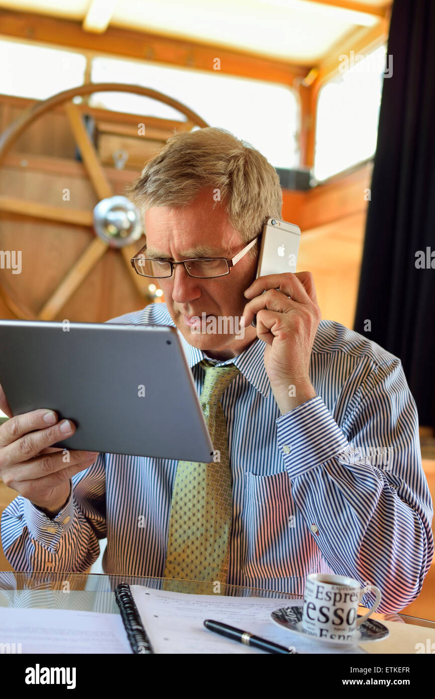 Serious mature man working in houseboat office using iPad tablet computer and iPhone 6 concentrates on the screen - Stock Image