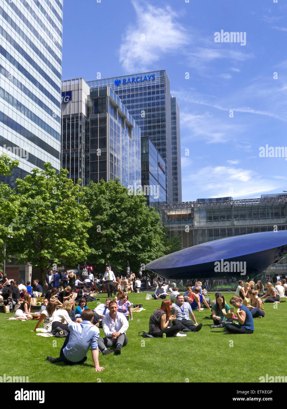 Canary Wharf workers taking a lunch break in summer sun on newly laid grass lawn with offices including Barclays - Stock Image