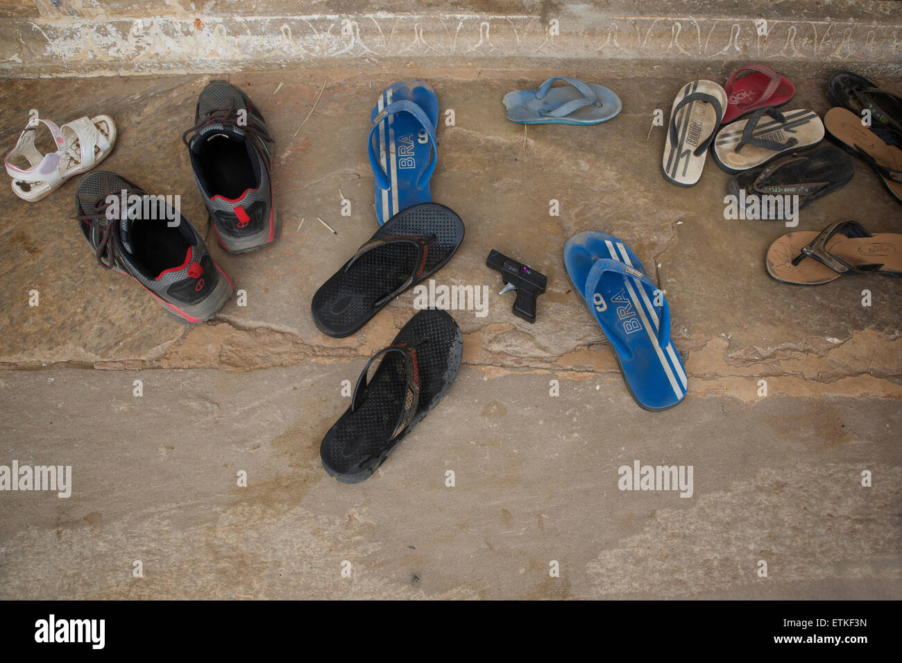 Footwear (and toy gun) left outside a temple. Mandawa, Shekawati region, Rajasthan India - Stock Image