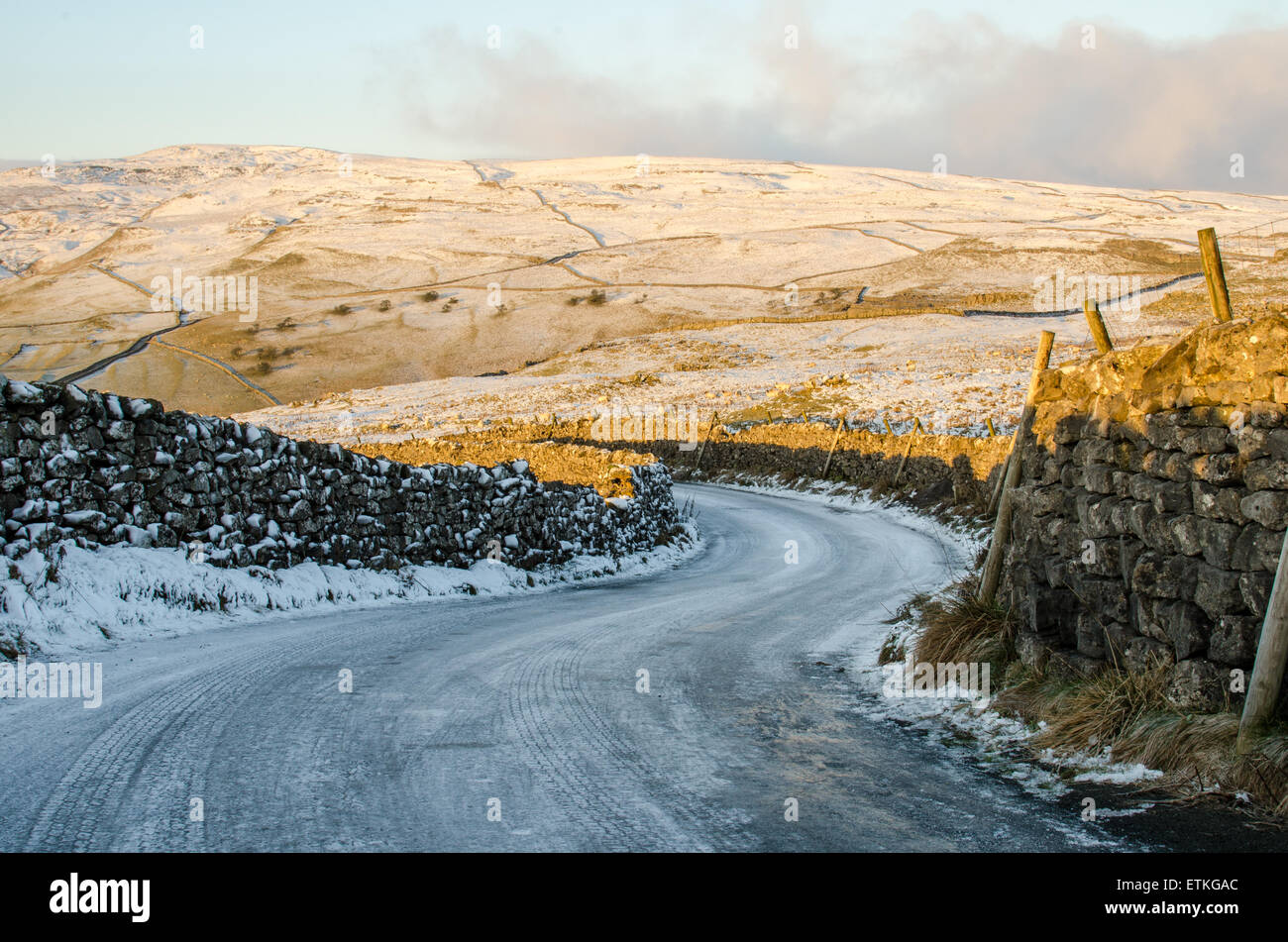 Sweeping bend covered in ice and snow on a road near Malham, Yorkshire - Stock Image