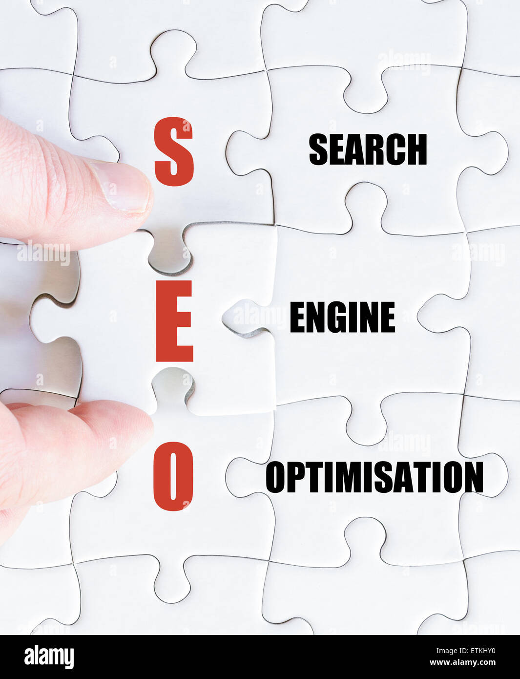Hand of a business man completing the puzzle with the last missing piece.Concept image of Business Acronym SEO as - Stock Image