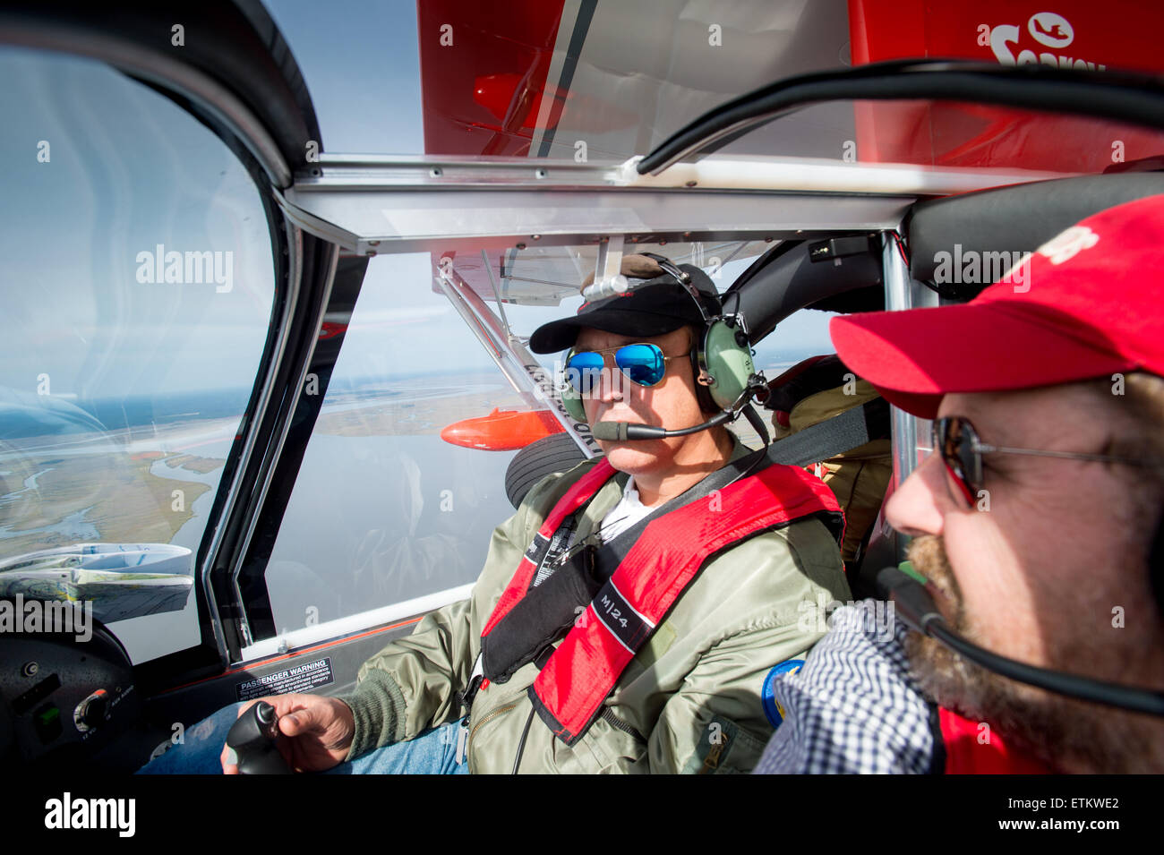 Male pilots in seaplane flying over Georgia, USA - Stock Image