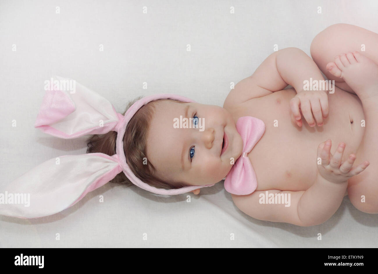 portrait of cute little happy baby boy with rabbit's ears lying on soft white bed, happy family concept - Stock Image