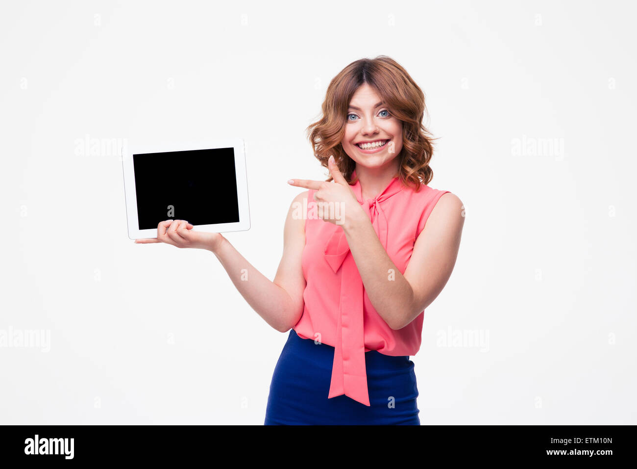 Happy woman pointing finger on blank tablet computer screen isolated on a white background. Looking at camera - Stock Image