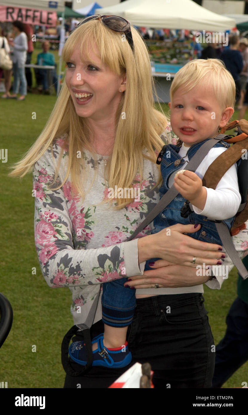 Woman and baby displaying contrasting demeanour/expressions at Churt fete, Churt Recreation Ground, Churt, Farnham, - Stock Image