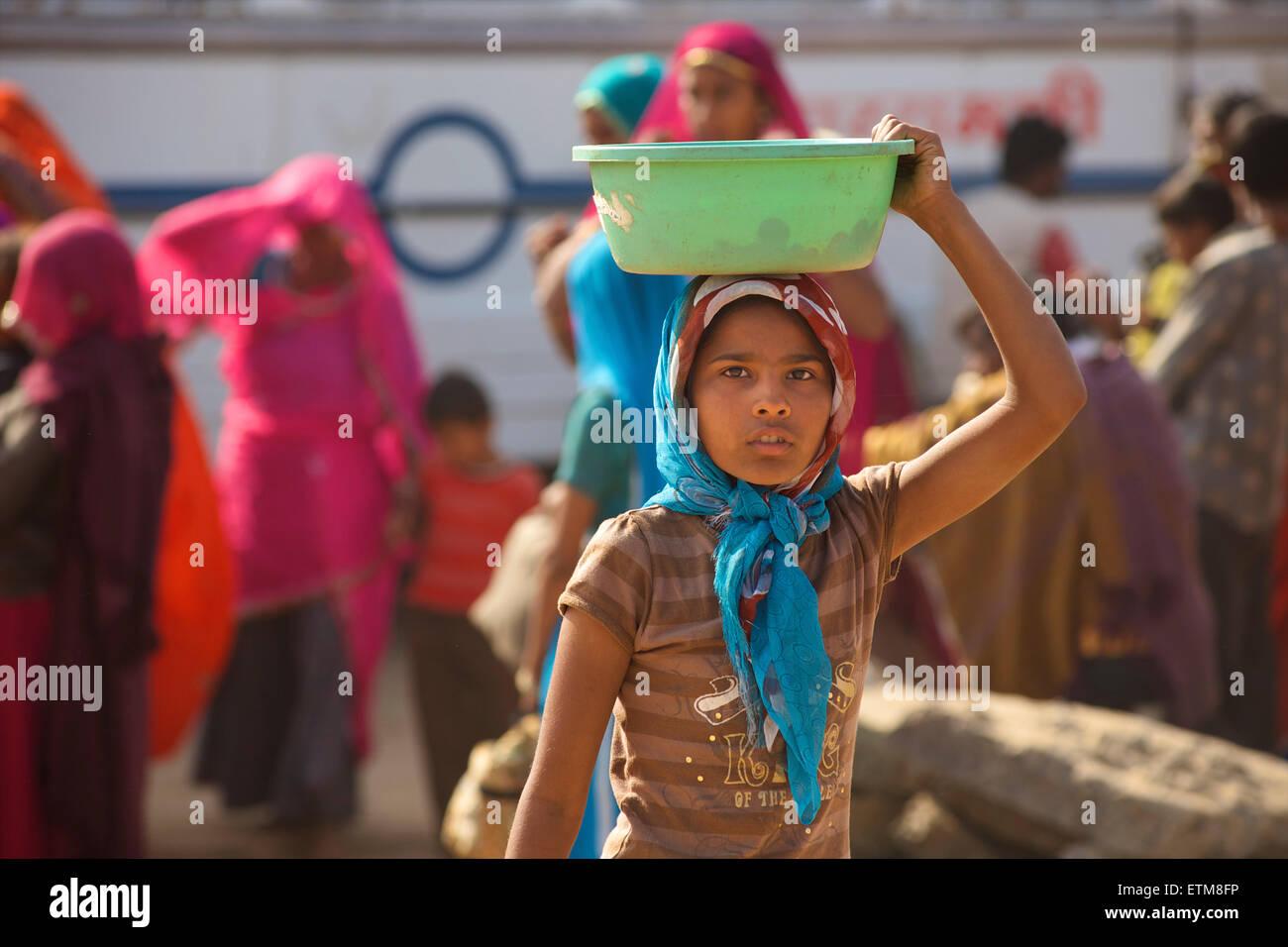 Indian girl collecting camel dung in a green bowl. Pushkar Camel Fair, Rajasthan, India - Stock Image