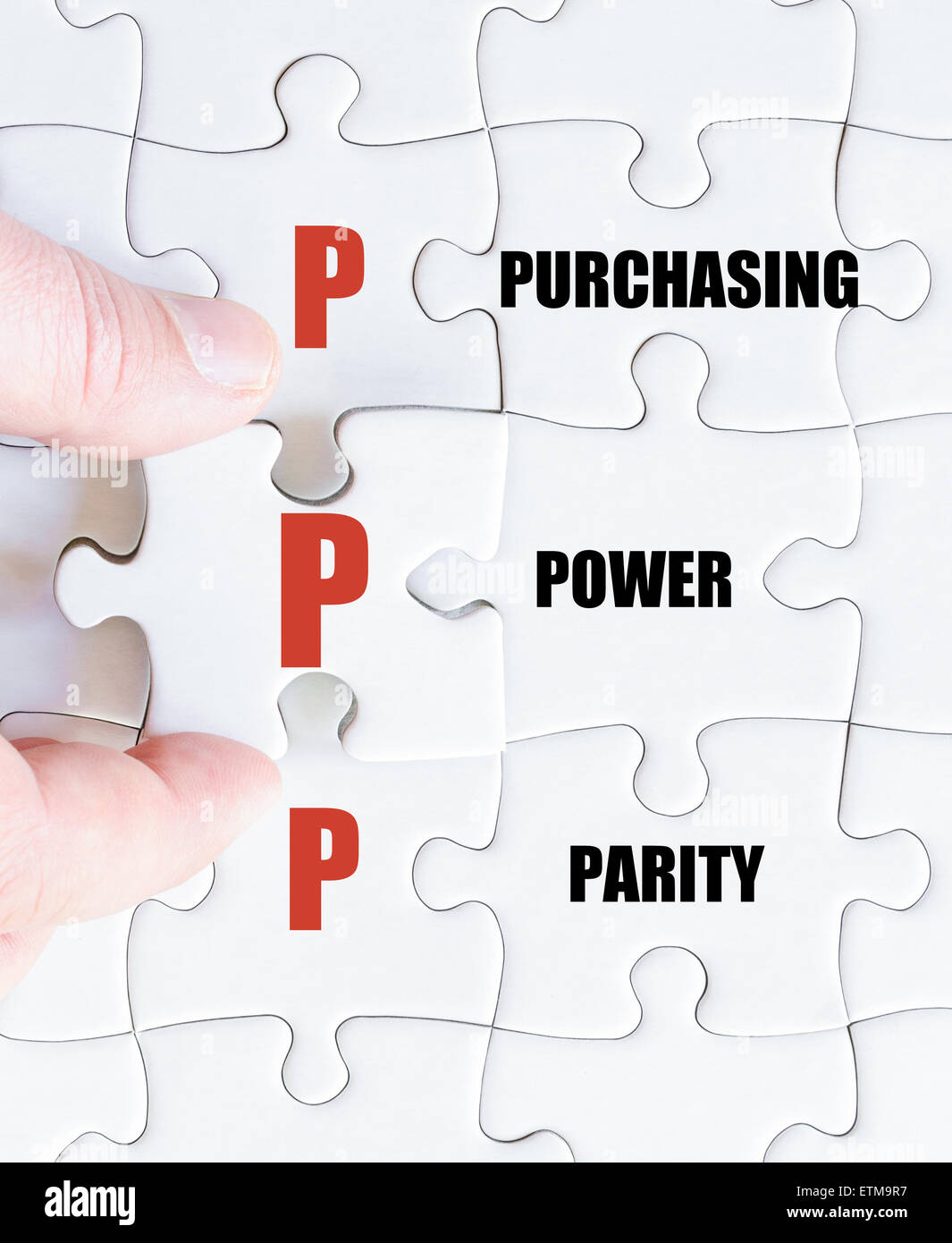 Hand of a business man completing the puzzle with the last missing piece.Concept image of Business Acronym PPP as - Stock Image