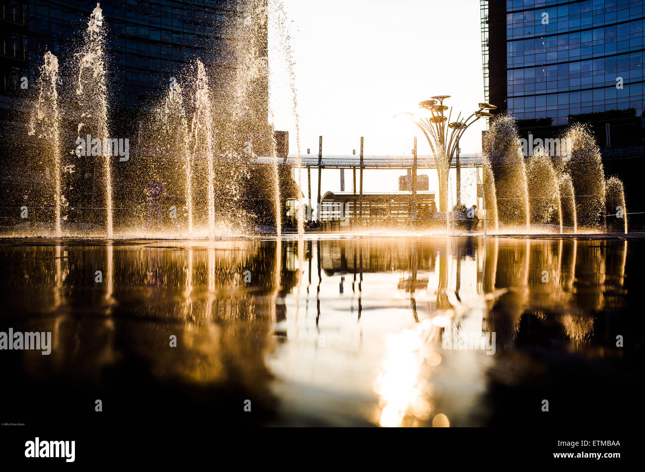 Many fountains splashing water over the square in Milan, Porta Nuova, Italy - Stock Image
