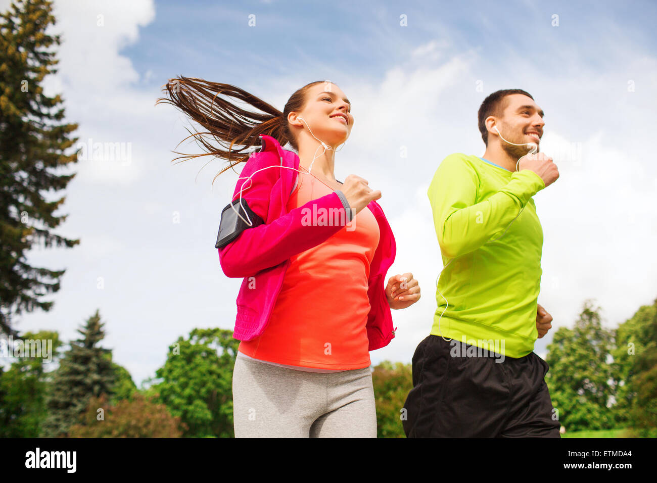 smiling couple with earphones running outdoors - Stock Image