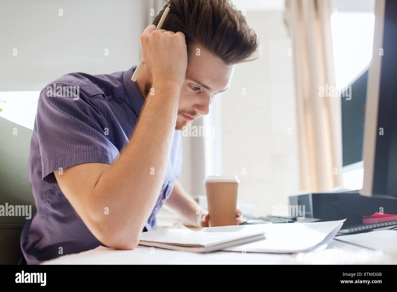 creative male office worker with coffee thinking - Stock Image