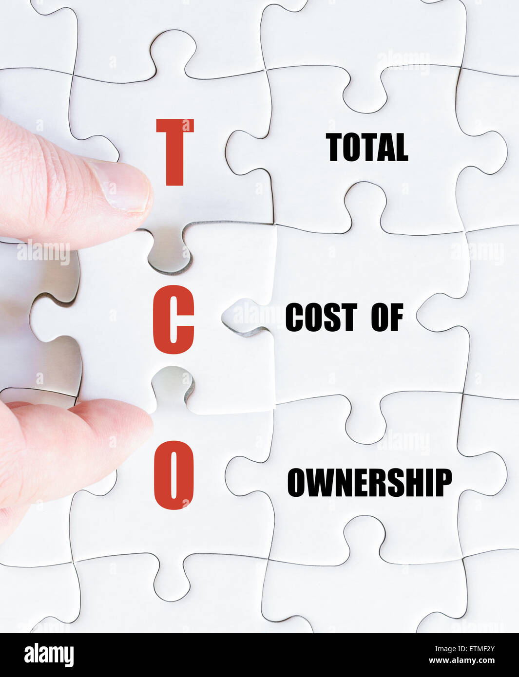 Hand of a business man completing the puzzle with the last missing piece.Concept image of Business Acronym TCO as Stock Photo