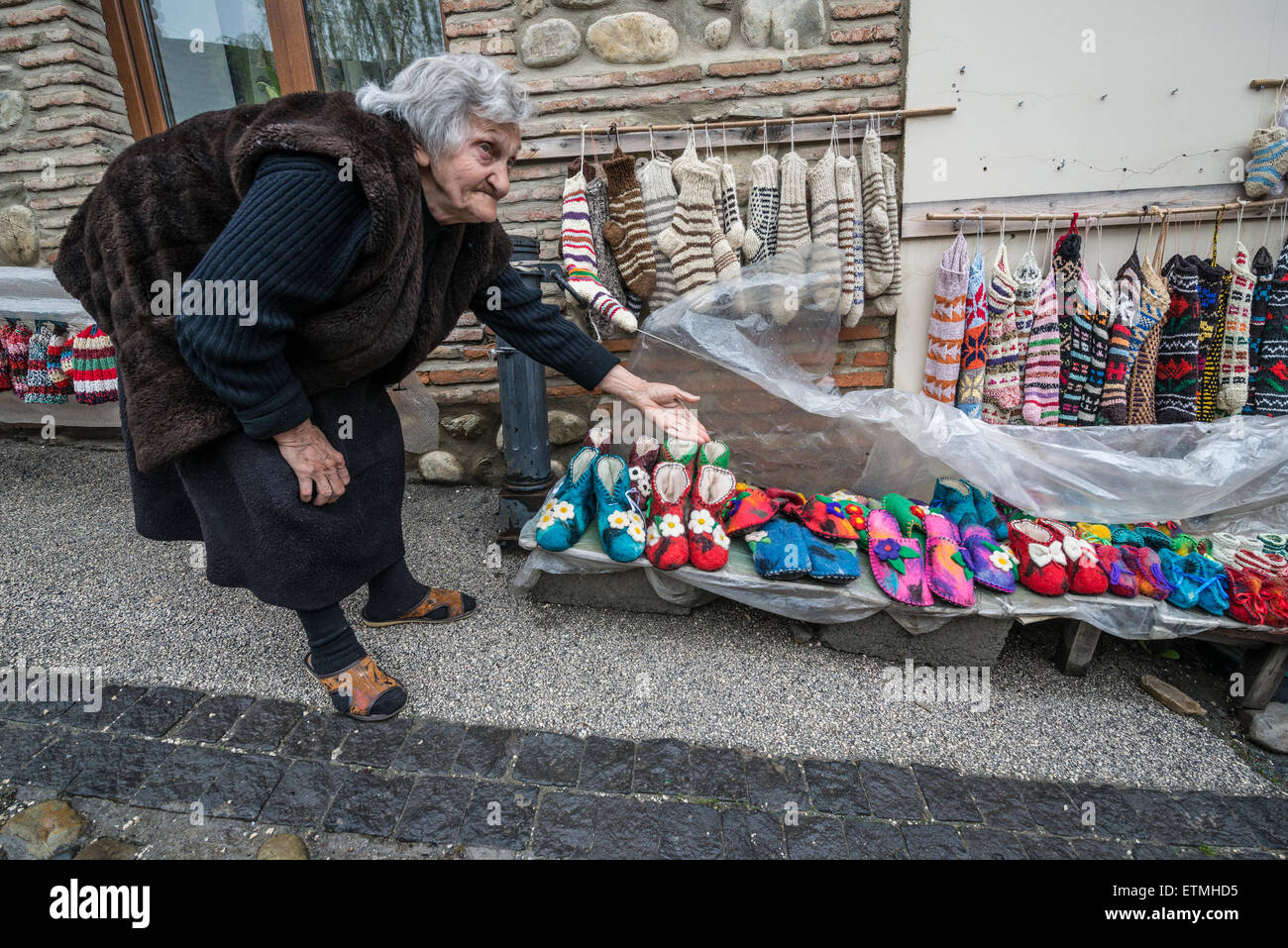 Old woman selling wool slippers and socks on souvenir stand in Sighnaghi, Kakheti region of Georgia - Stock Image