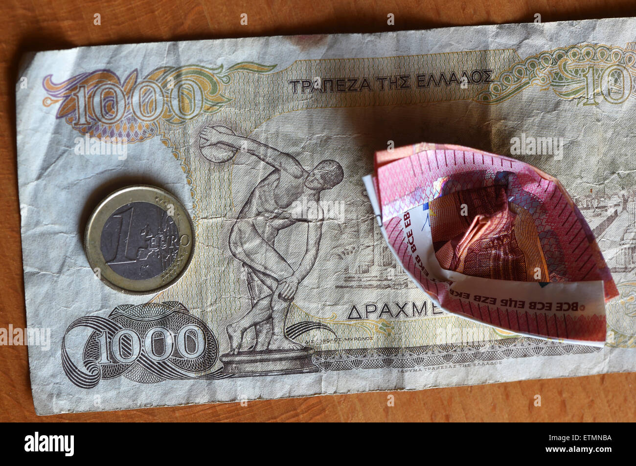 Berlin, Germany. 14th June, 2015. ILLUSTRATION - A euro coin and a ten euro bill which has been folded into a boat lies on a 1000 Greek drachma bill in Berlin, Germany, 14 June 2015. Photo: Jens Kalaene/dpa/Alamy Live News Stock Photo