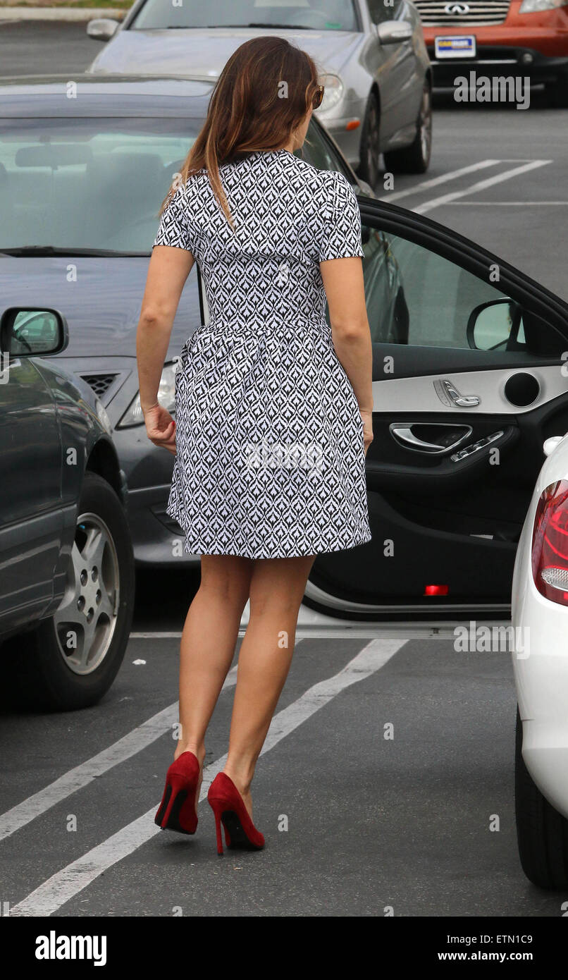 Kelly Brook dons a zipped fronted light summer dress showing her toned legs walking in red high heels on her way - Stock Image